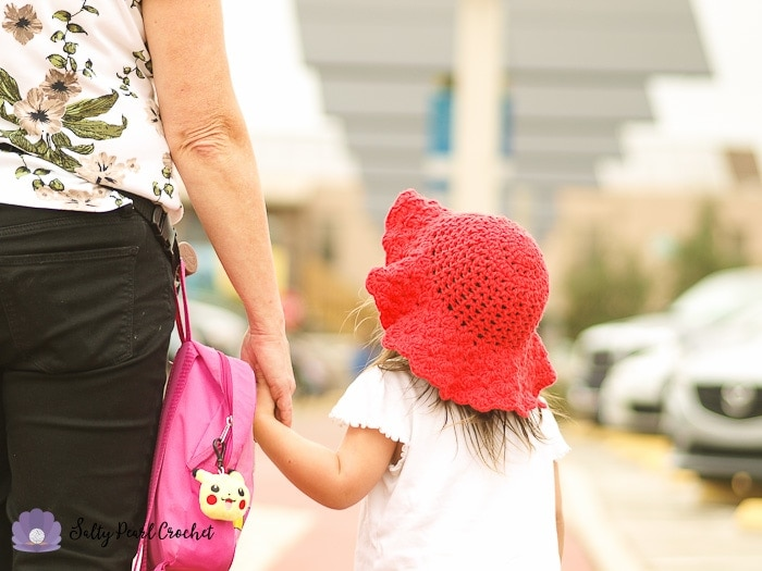 My daughter walking with her Grandmother while wearing her Scalloped Toddler Beach Hat
