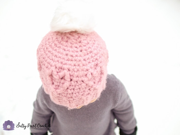 girl in the snow wearing a pink crochet heart hat with a pompom