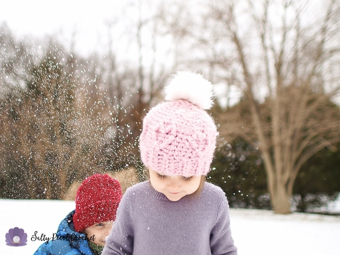 Girl wearing a pink crochet hat in the snow