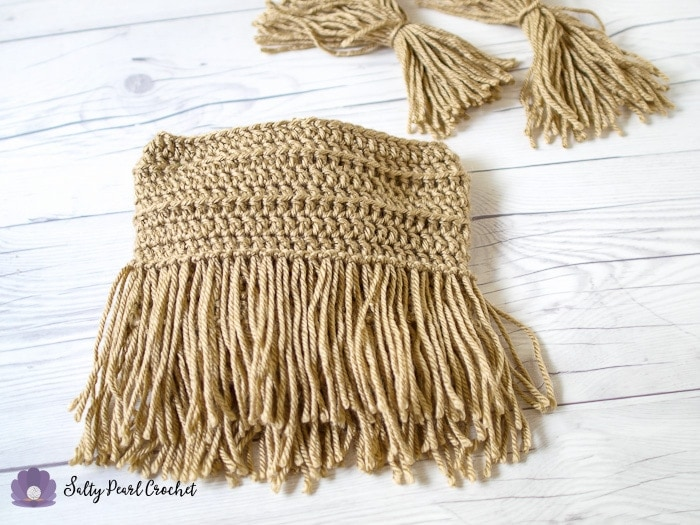 The crochet fringe clutch after adding two rows of fringe with the larks head knot.