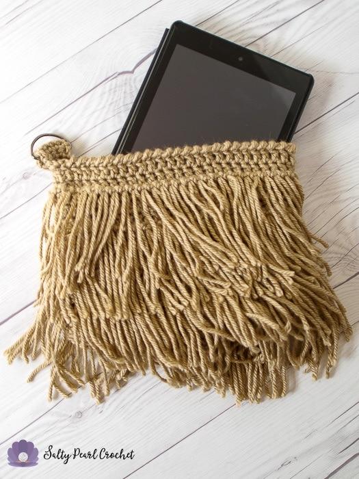 Crochet Fringe Clutch Pattern holding a tablet