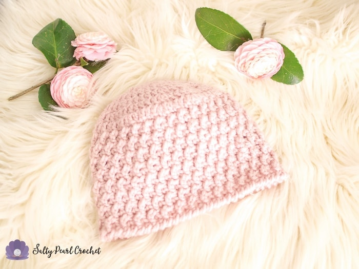 Pink textured crochet hat and three camellia blooms on a sheepskin rug.