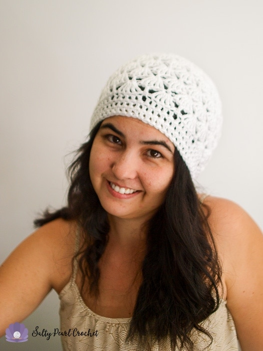 Woman smiling wearing a white crochet slouch hat