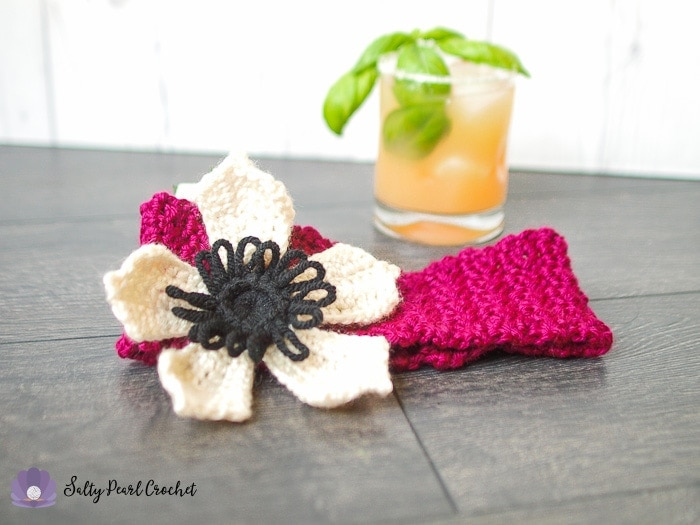 A white crochet anemone flower on a red headband