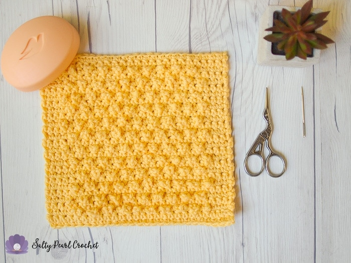 Yellow textured crochet washcloth on a table with soap and scissors