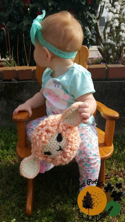 A cute baby holding a sensory sheep crochet baby toy