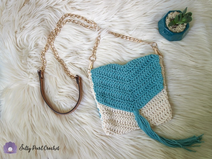 Full zoomed out view of the boho crochet purse laid out flat on a furry surface with a succulent plant.