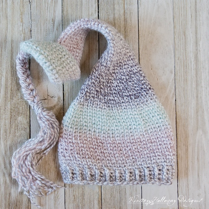A striped baby elf hat with a tassel on a wood surface.
