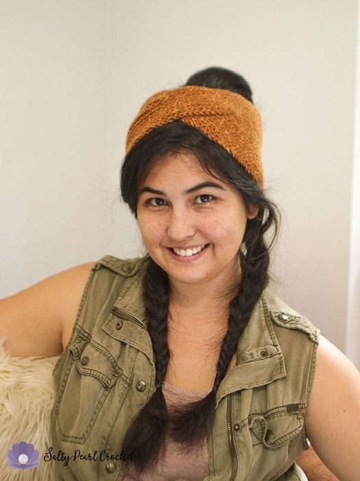 Woman smiling at the camera wearing a boho crochet headwrap over a messy bun and double braid hairstyle.