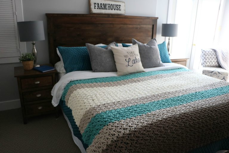 Chunky striped crochet afghan pattern by MJs Off the Hook Designs on a king bed.