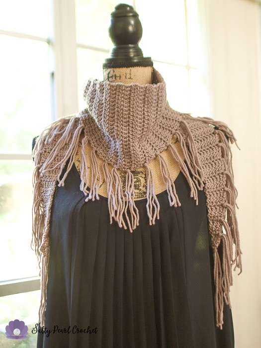 A crochet triangle scarf with fringe on a mannequin in a sunny window.