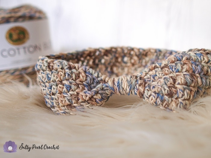 A Crochet Ear Warmer Pattern sample sitting in front of a cake of Lion Brand Comfy Cotton Blend Yarn