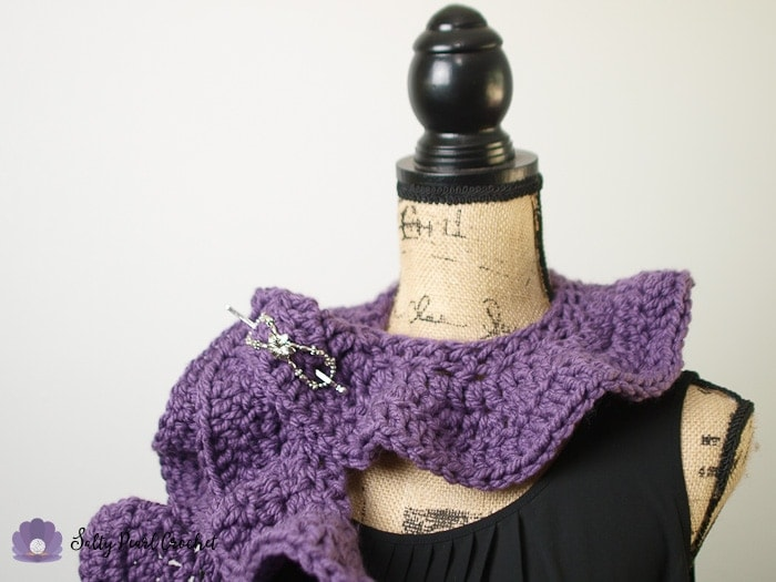Tight shot showing the ruffle scarf wrapped around the neck of a bust form.