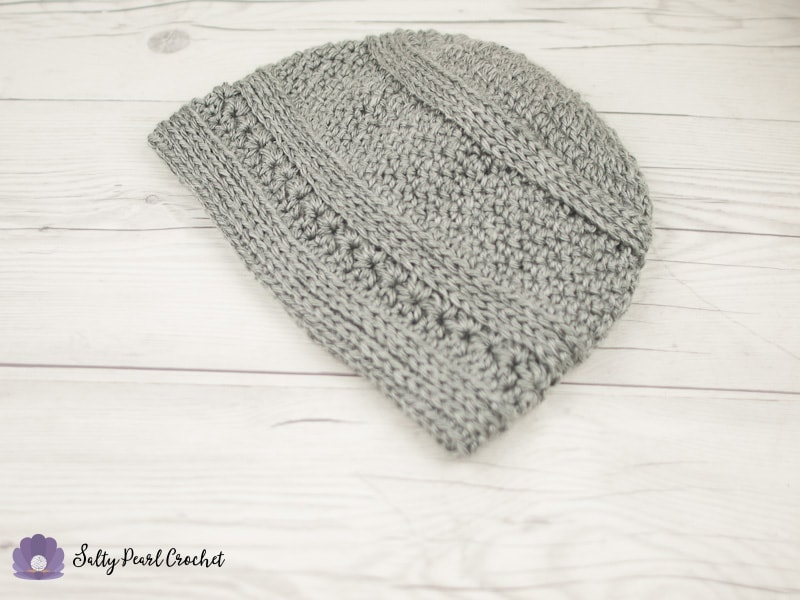 a gray crochet hat for men laid flat on a white wood desktop