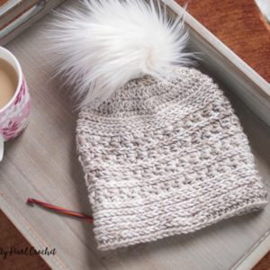 Crochet star stitch hat on a tray with a coffee mug