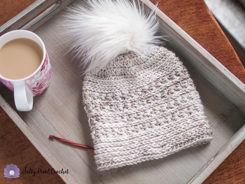 Crochet star stitch hat on a tray with a coffee mug