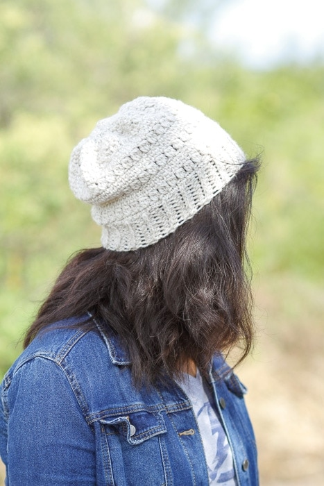 Side view of a woman wearing a crochet slouchy hat facing away from the camera.