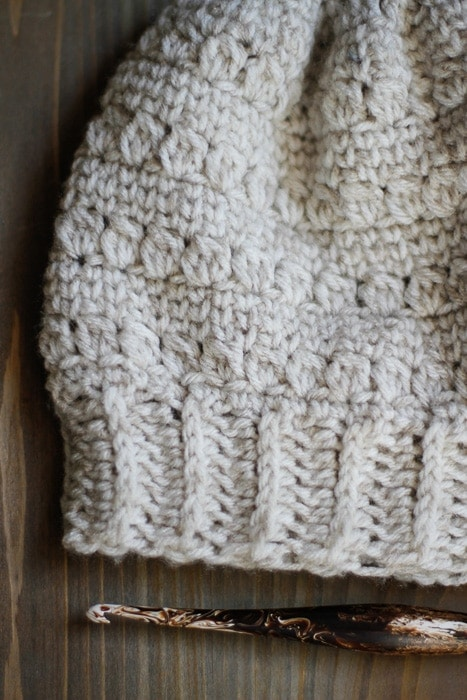 Close up of a crochet slouchy hat and a streamline crochet hook.