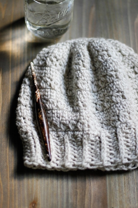 A white crochet slouchy hat on a desk with a crochet hook and a glass of water.