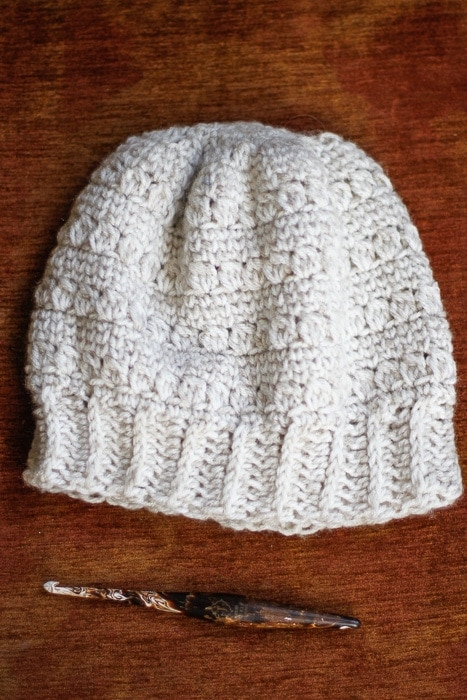 Cream colored crochet hat displayed with a crochet hook.