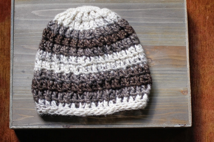 Chunky yarn crochet beanie on a wooden tray.