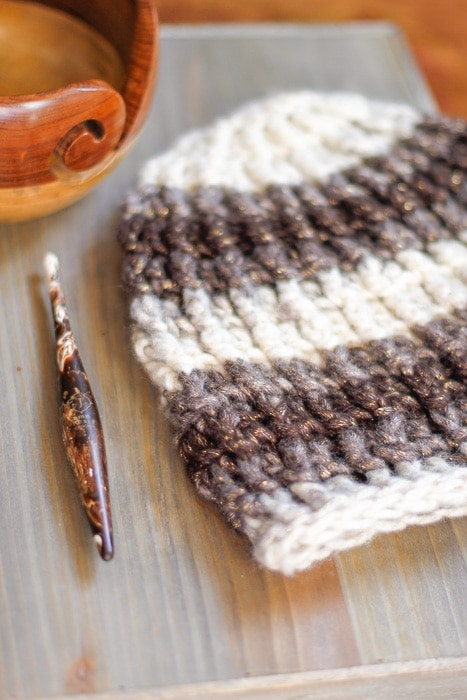 A Furls Streamline Swirl crochet hook displayed with a yarn bowl and a ribbed crochet beanie hat.
