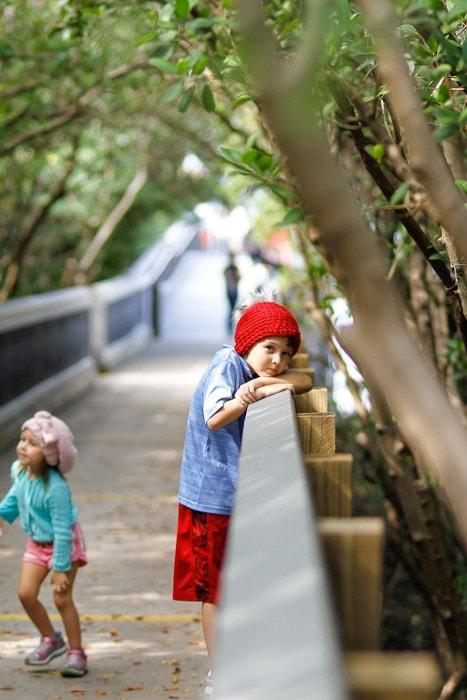 Boy on a bridge wearing a red crochet slouchy beanie