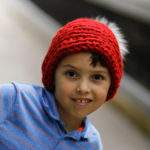 Boy wearing a red crochet slouchy hat