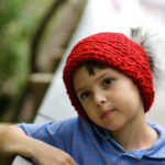 Boy wearing a hat made from an easy crochet slouchy hat pattern.