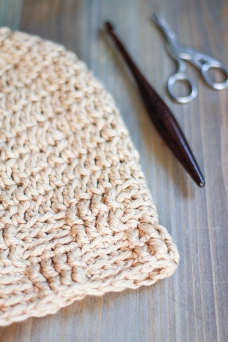 A textured crochet beanie pattern displayed with a crochet hook and crane scissors.