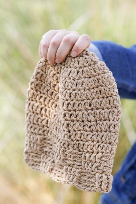 Hand holding a crochet basketweave stitch beanie.
