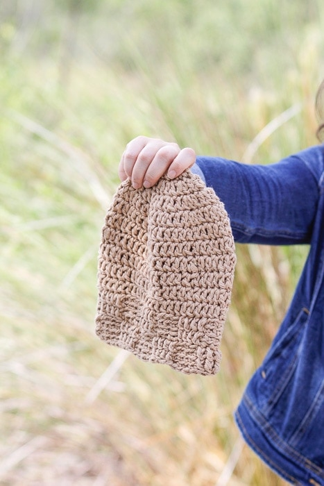 Woman holding a crocheted beanie made with the basket weave stitch.