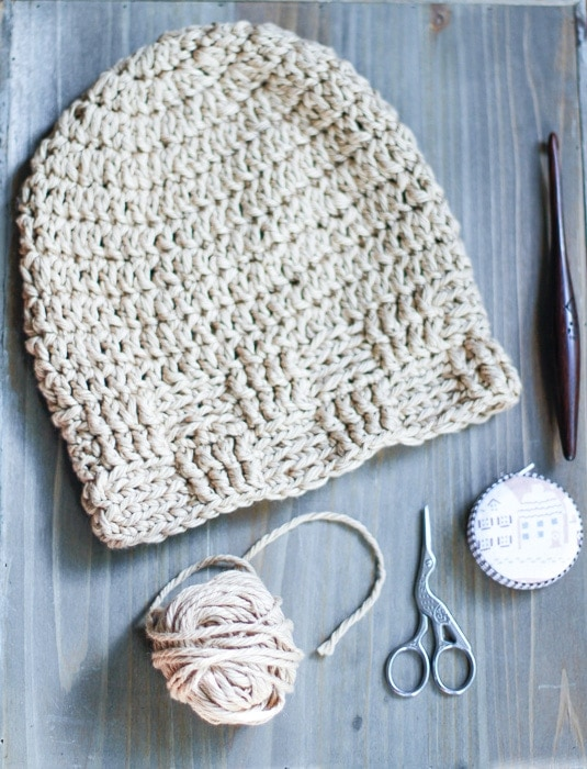 Crochet basketweave stitch beanie on a desk with a ball of yarn, crane scissors, a measuring tape, and a crochet hook.