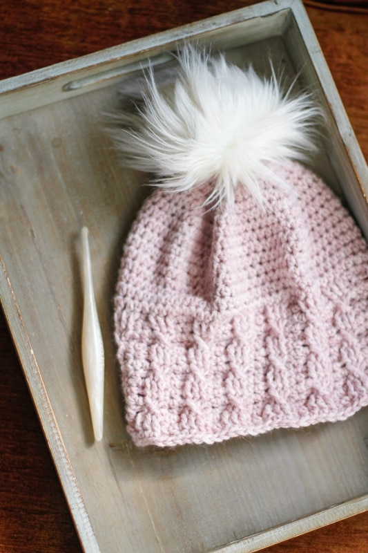 A sample of the Simple Cable Brimmed Beanie laid flat on a tray with a crochet hook.