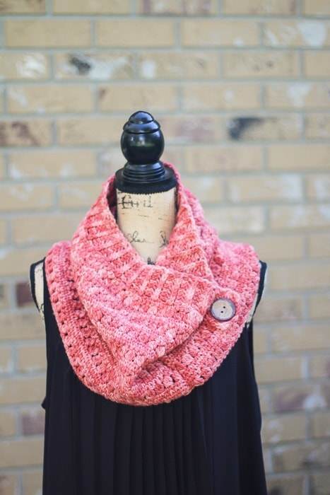 A pink crochet cowl with a button displayed on a mannequin.
