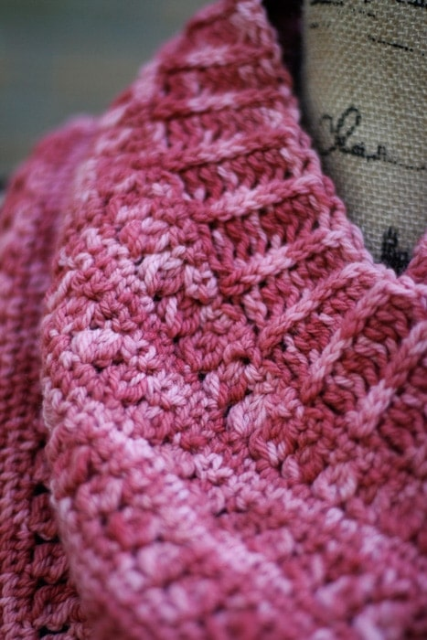 Close up photo of crochet ribbing, cluster stitches, and the waistcoat stitch on a crochet cowl pattern.