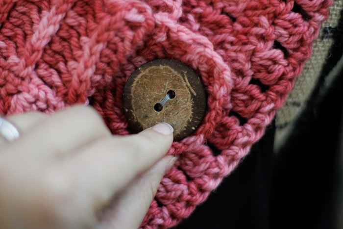 Showing the large decorative button on this  buttoned crochet cowl pattern.
