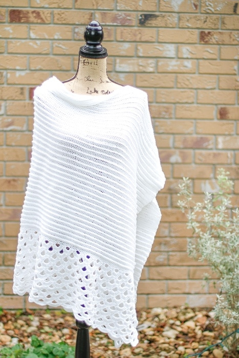 A crochet poncho with lace stitching on a mannequin.