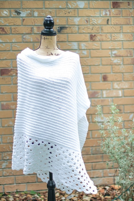 A simple crochet poncho made from a rectangle displayed on a mannequin.