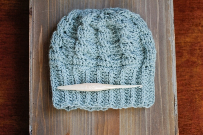 A white crochet hook lying on top of a cabled crochet hat.