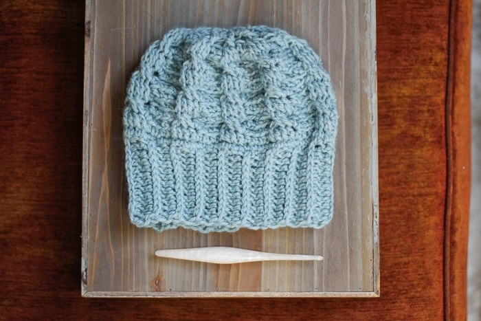 A cabled crochet hat with a large brim laid flat on a tray beside a crochet hook.