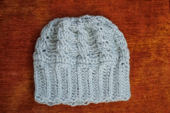 A mint green crochet hat made with wide crochet ribbing and a simple crochet cable braid.