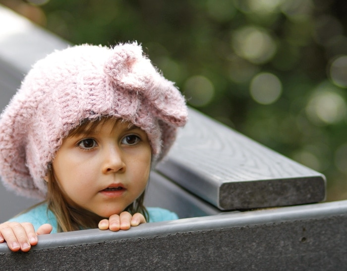 5 year old girl wearing a pink crochet slouchy hat with a bow.