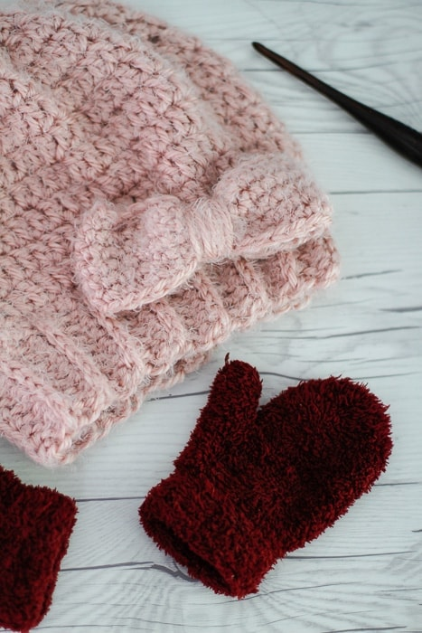 A close up of the crocheted bow from the easy slouchy bow hat pattern on a table with mittens and a crochet hook.