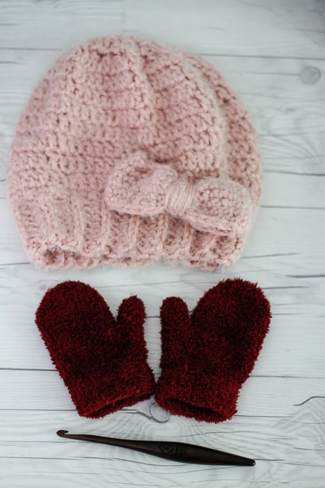 A sample of the easy slouchy bow hat crochet pattern laid on a table with a pair of mittens and a crochet hook.