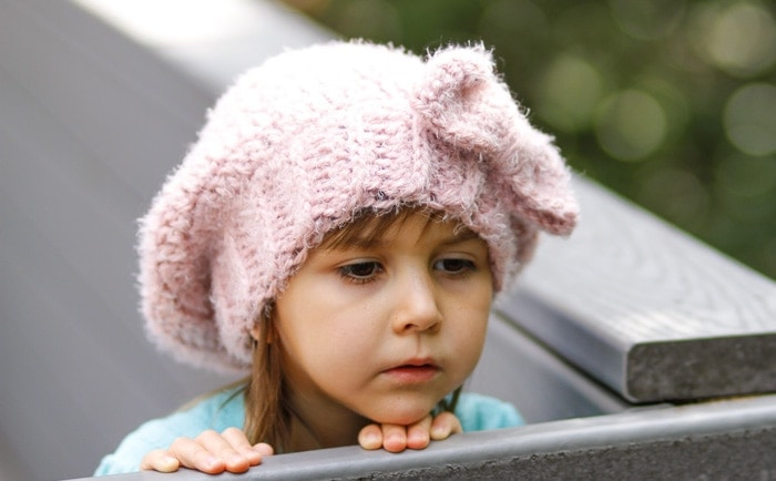 A young girl looking over a railing while wearing a pink crochet slouch beanie.