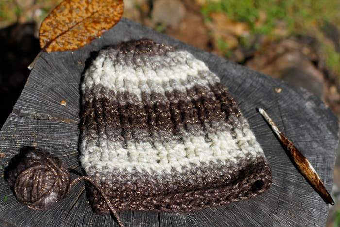 Photo of a crochet cable hat with a crochet hook and ball of yarn.