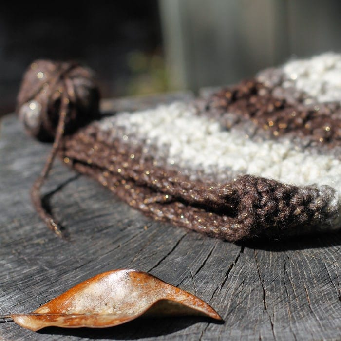Closeup of a cabled crochet hat brim on a wood surface.