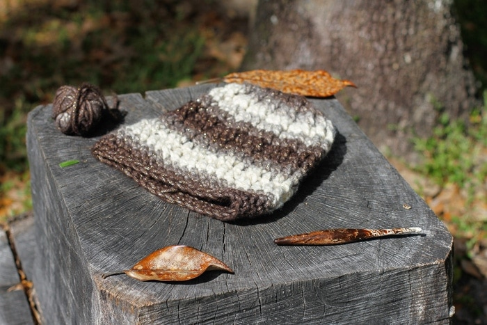 A ball of yarn, crochet hook, and a simple crochet cable hat on a stump.