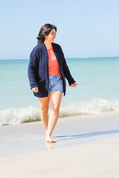 Woman wearing an easy crochet cardigan she made walking on the beach.